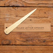 Brass letter opener that doubles as a ruler; one side engraved in cm up to 15cm, the other side up to 6 inches.